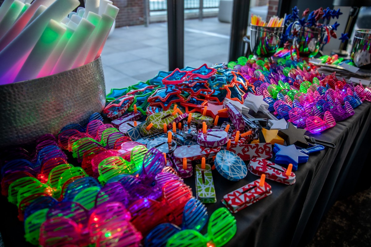 neon 80s sunglasses and noisemakers displayed on a table